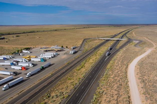 Horizontale panoramavrachtwagens stoppen op een rustplaats in de buurt van de snelweg in woestijn, arizona, vs