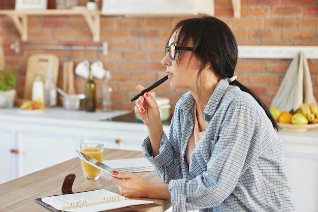 Horizontale portret van brunette vrouw draagt losse casual shirt, kijkt peinzend opzij