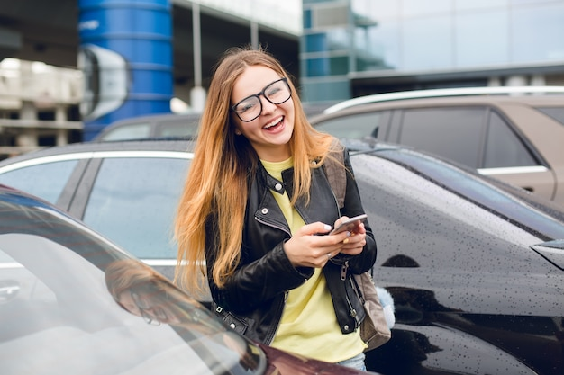 Horizontale portret van een jong meisje met lang haar in glazen lopen op parkeerterrein. ze draagt een gele trui en een zwarte jas. ze lacht naar de camera en houdt de telefoon in handen. Gratis Foto