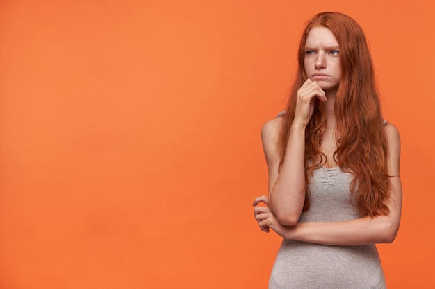 Horizontale portret van jonge mooie vrouw met golvend foxy haar opzij kijken en fronsen, met twijfels in gedachten poseren over oranje achtergrond in casual grijs shirt