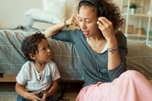 Horizontale portret van mooie jonge spaanse vrouw luisteren naar muziek in draadloze koptelefoon zittend op de vloer met haar knappe zoontje. gelukkige familie plezier thuis