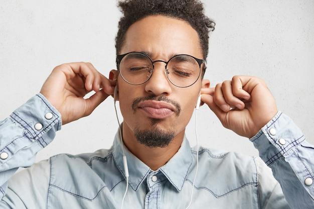 Horizontale portret van ontspannen modieuze mannelijke tiener met baard en snor, draagt grote bril,