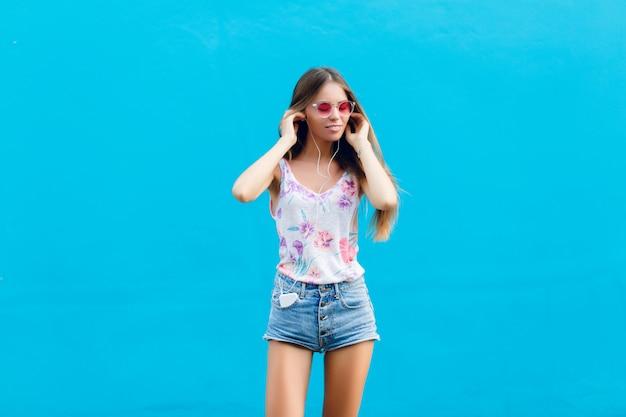Horizontale portret van schattig stijlvol meisje op blauwe achtergrond staat en luistert naar muziek op oortelefoons op smartphone