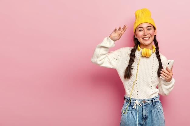 Horizontale schot van aantrekkelijke gemengd ras vrouw houdt moderne mobiel, dansen en koptelefoon draagt om nek, vormt tegen roze achtergrond, kopie ruimte