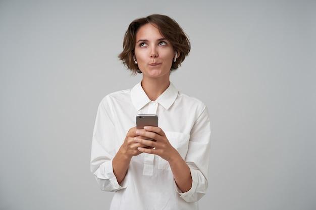 Horizontale schot van aantrekkelijke jonge dame met kort kapsel, gekleed in een wit overhemd, dromerig opzij kijken tijdens het controleren van sociale netwerken met haar smartphone, geïsoleerd
