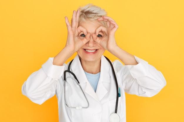 Horizontale schot van aantrekkelijke vrolijke middelbare leeftijd vrouwelijke medische werker dragen witte jas en stethoscoop om nek met plezier, positieve houding tonen, verrekijker met vingers maken, glimlachend