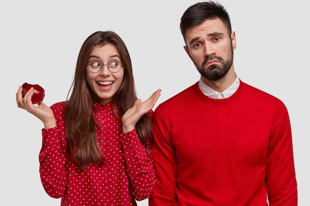 Horizontale schot van gediplomeerde ongeschoren jongeman fronst gezicht, draagt rode trui, gelukkige dame eet heerlijke appel, kijkt vrolijk opzij