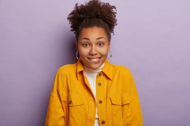 Horizontale schot van gelukkig gekrulde haired vrouw glimlacht vreugdevol, lippen bijt, geniet van aangenaam moment, stijlvolle gele outfit draagt, vormt tegen paarse achtergrond.