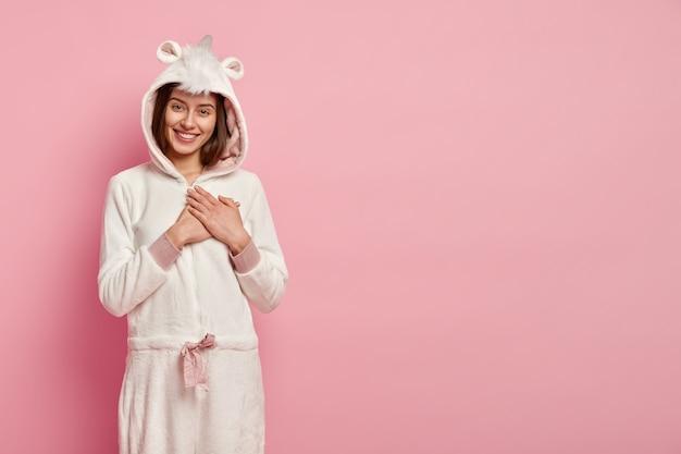 Horizontale schot van lachende jonge vrouw heeft een positieve glimlach, houdt de handen op de borst, drukt oprechte emoties uit, draagt een wit kigurumi-kostuum met oren, staat over roze muur met lege ruimte