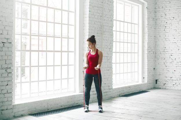 Horizontale schot van mooie atletische jonge europese vrouw met haar knoop trainen in de sportschool, haar spieren opwarmen met behulp van yoga riem, staande op houten vloer
