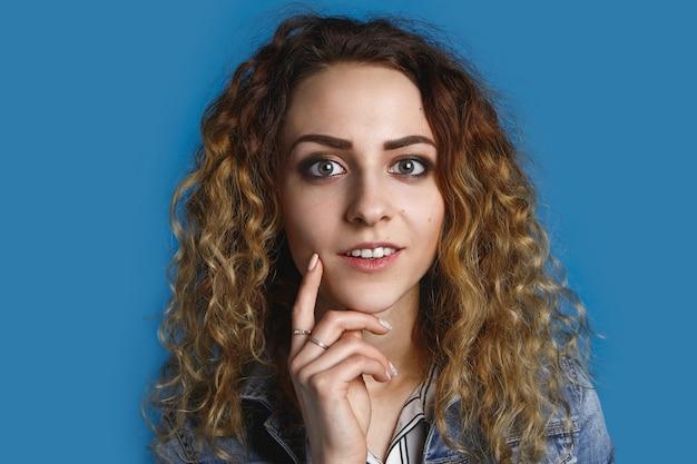 Horizontale schot van positieve aantrekkelijke groene ogen jonge europese vrouw gekleed stijlvol hand onder haar kin met mysterieuze peinzende glimlach alsof ze een geweldig idee