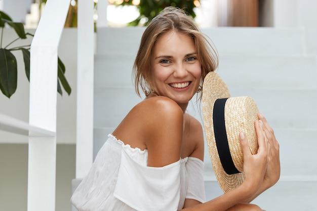 Horizontale schot van schattige lachende vrouw draagt modieuze witte blouse, houdt zomerhoed van stro in handen, besteedt vrije tijd in het hotel als recreëren in hete exotische land tijdens onvergetelijke vakanties