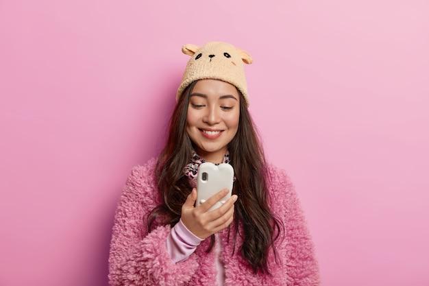 Horizontale schot van tedere tevreden vrouw gebruikt moderne mobiele telefoons, controleert e-mail, ontvangt bericht van vriend, stuurt feedback, heeft een aangename glimlach op het gezicht