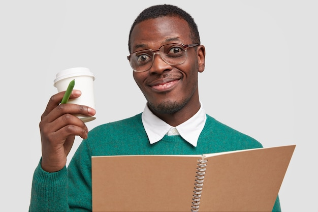 Horizontale schot van tevreden donkere jongeman met stoppels, draagt vierkante bril, houdt afhaalmaaltijden koffie, pen en notitieblok
