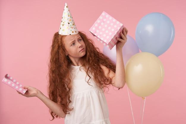 Horizontale schot van vrouwelijke roodharige jongen met krullend haar in verjaardag glb viert vakantie, kijkt in lege geschenkdoos en wordt teleurgesteld, staande over roze studio met gekleurde ballonnen