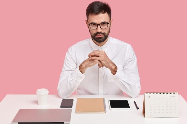 Horizontale schot van zelfverzekerde knappe bebaarde jongeman in wit formeel overhemd, transparante bril draagt, zit op het bureaublad, perfectionistisch