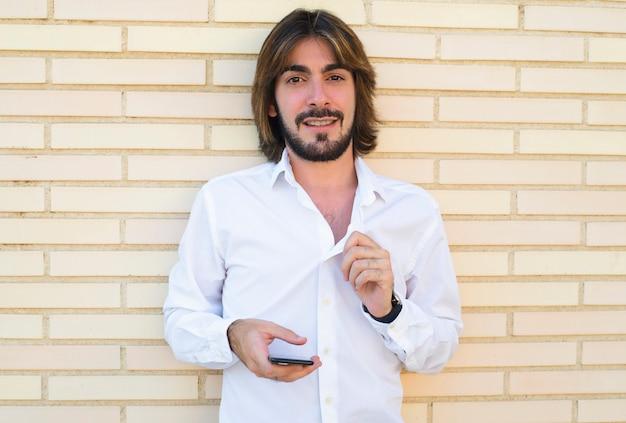 Horizontale shoot van aantrekkelijke jonge man met lang haar, baard, wit shirt, leunend tegen de muur en met een smartphone in zijn hand kijkt naar de camera glimlachen.