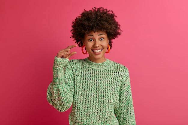 Horizontale shot van donkere huid afro-amerikaanse vrouw toont klein bedrag gebaar, maatregelen klein item, lacht aangenaam, draagt gebreide trui, geïsoleerd op roze muur. lichaamstaal concept