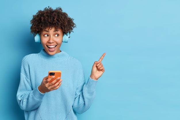 Horizontale shot van goed uitziende afro-amerikaanse vrouw voelt zich erg blij moderne smartphone in de hand houdt stereo koptelefoon punten opzij op lege ruimte op blauwe achtergrond. vrije tijd concept