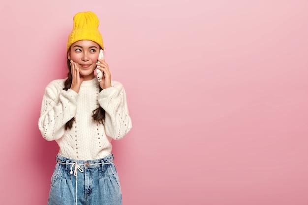Horizontale shot van goed uitziende aziatische meisje maakt telefoongesprek, geniet van aangenaam gesprek via mobiel, gekleed in vrijetijdskleding, staat binnen tegen roze achtergrond.