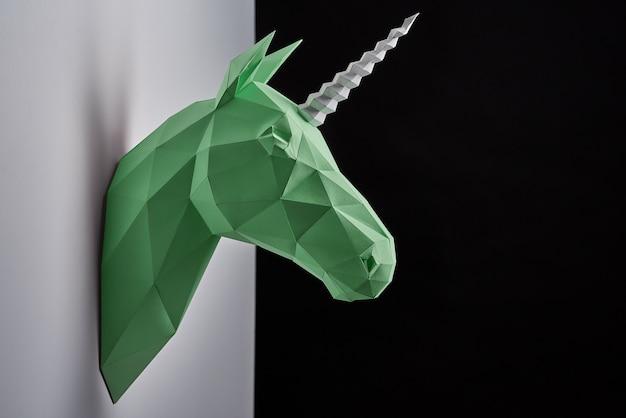 Horizontale spruit van het hoofd die van de groene eenhoorn op grijze in de schaduw gestelde muur hangen.