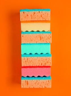 Horizontale stapel gekleurde schoonmaaksponzen geïsoleerd op een oranje achtergrond. minimalistisch reinigingsconcept
