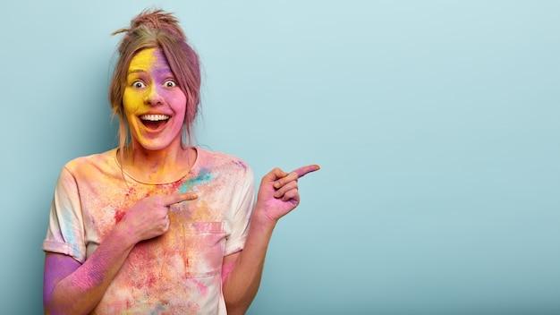 Horizontale studio-opname van gelukkige europese vrouw wijst naar de zijkant, bedekt met holi-kleuren