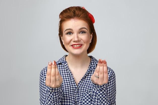 Horizontale studio-opname van grappige emotionele jonge glamourorus europese vrouw met stijlvol kapsel en lichte make-up opgewonden uitroepen, vingers vasthouden alsof ze geld tellen, winst maken op grote verkoop