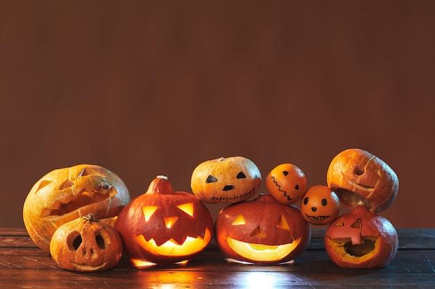 Horizontale studio-opname van halloween stillevensamenstelling gemaakt van gesneden pompoenen en mandarijnen op bruin oppervlak, kopieer ruimte