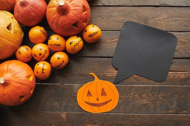 Horizontale top-down shot van gesneden pompoenen, mandarijnen papier jack-o'-lantern met zwarte quote box liggend op donkerbruine houten tafel