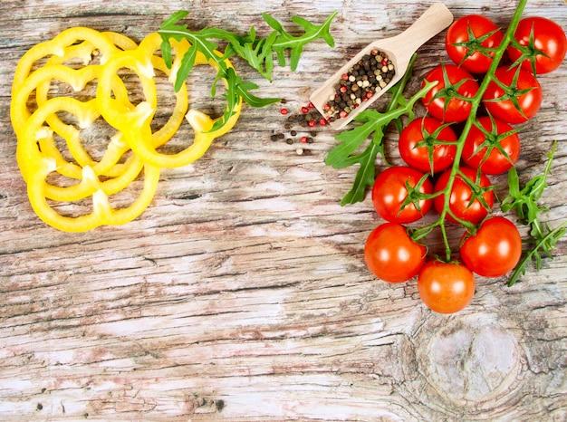Horizontale voedselbanner met kersentomaten, gele paprika, arugula en peperbollen.