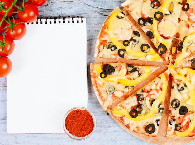Horizontale voedselbanner met kersentomaten, gesneden pizza, kruid en notitieboekje
