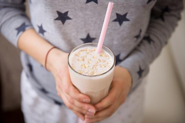 Horizontale weergave jonge vrouw met een groot glas gezonde smoothie geserveerd met een rietje en haver