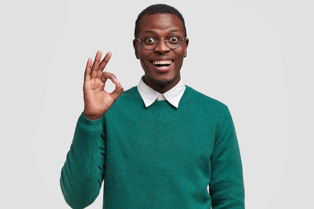 Horizontale weergave van aantrekkelijke jonge zwarte man met brede glimlach, toont oke gebaar, zegt oke, houdt van iemands idee
