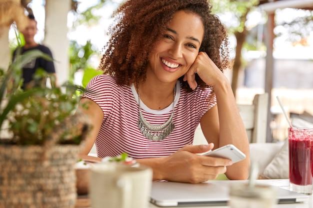 Horizontale weergave van aantrekkelijke tiener heeft een positieve glimlach op het gezicht