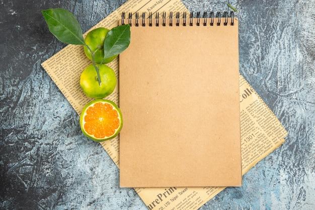 Horizontale weergave van bruin notitieboekje en verse citroenen op krant op grijze achtergrond