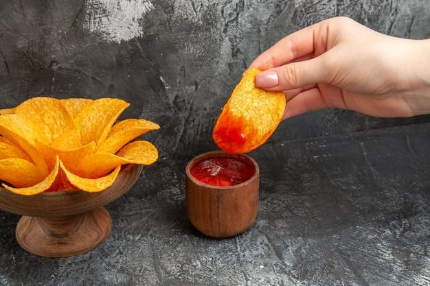 Horizontale weergave van chips en kleine ketchupkom op grijze tafel