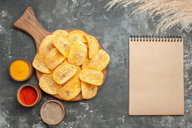 Horizontale weergave van chips, kruiden en mayonaise met ketchup en noteboo op grijze tafel