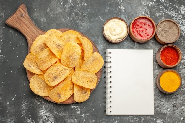 Horizontale weergave van chips, kruiden en mayonaise met ketchup en notebook op grijze tafel