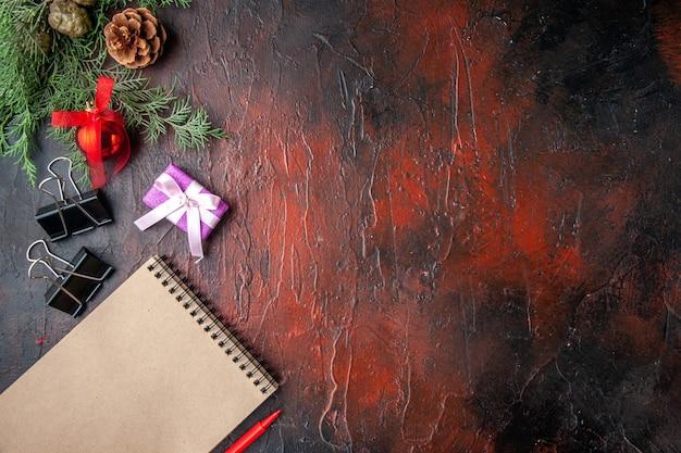 Horizontale weergave van decoratieaccessoires van dennentakken en cadeau naast notitieboekje met pen op donkere achtergrond