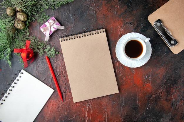 Horizontale weergave van dennentakken, een kopje zwarte thee-decoratieaccessoires en een cadeau naast notitieboekjes op een donkere achtergrond