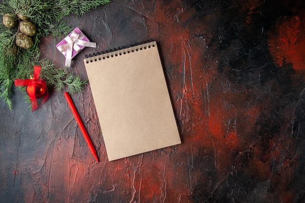 Horizontale weergave van dennentakken met decoratieaccessoires en cadeau naast notebook op donkere achtergrond