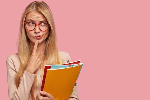 Horizontale weergave van doordachte schoolmeisje portemonnees lippen, houdt wijsvinger op kin, draagt een ronde bril