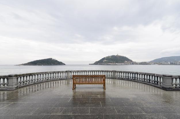 Horizontale weergave van een enkele bank op een uitkijkpunt vanaf een concha-strand, spanje
