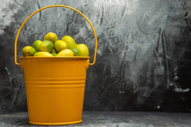Horizontale weergave van een gele emmer vol verse groene mandarijnen op grijze achtergrond