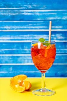 Horizontale weergave van een glas met verfrissende aperol spritz cocktail met munt en sinaasappelbladeren.