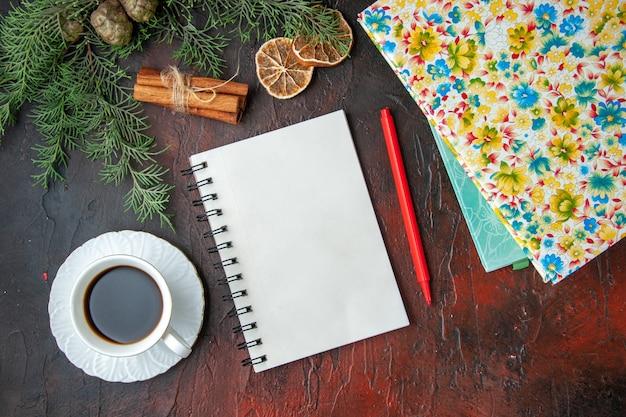 Horizontale weergave van een kopje zwarte thee gesloten notitieboekje met pen, kaneellimoenen, een bal touw en boeken op een donkere achtergrond
