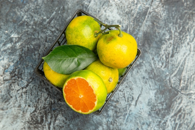 Horizontale weergave van een mand vol verse groene mandarijnen en in tweeën gesneden mandarijn op grijze achtergrond