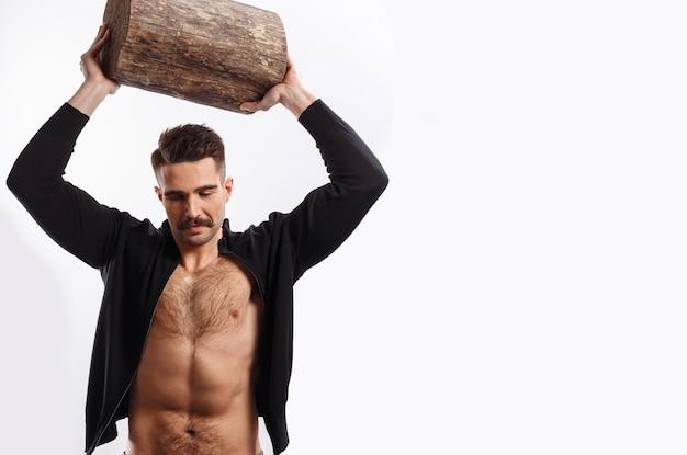 Horizontale weergave van een sterke, atletische, sexy man met snor, met naakte torso, stijgen op een boomstam boven het hoofd, op witte achtergrond.