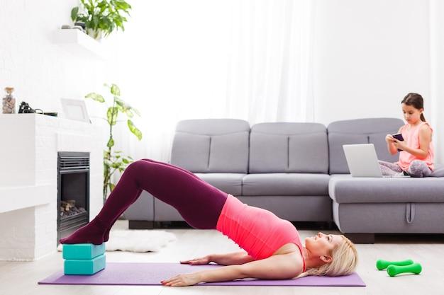 Horizontale weergave van een vrouw die thuis yoga doet